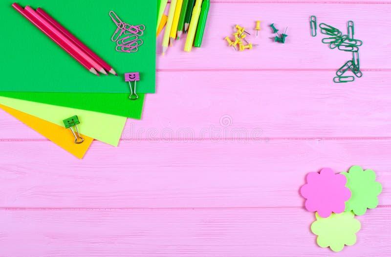 Ellow und grüne Bleistifte, Filzstifte, Briefpapier, Büroklammern, Briefpapiernägel, Filz und Lächeln auf rosa hölzernem Hintergr lizenzfreies stockfoto