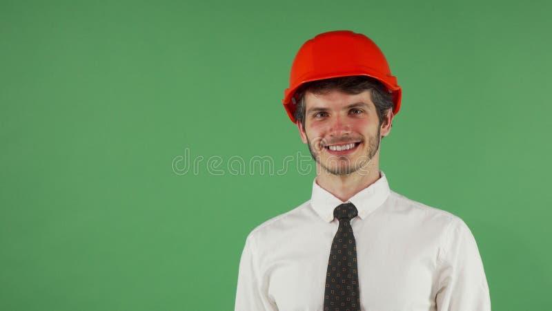 Elmetto protettivo d'uso dell'ingegnere maschio bello allegro che sbatte le palpebre alla macchina fotografica immagini stock