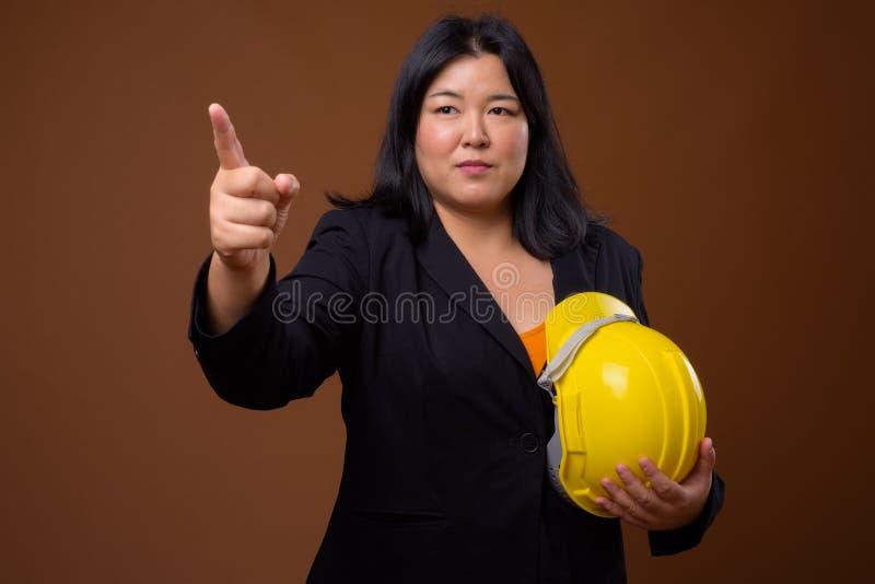 Elmetto protettivo della tenuta della donna di affari e dito asiatici indicare fotografie stock