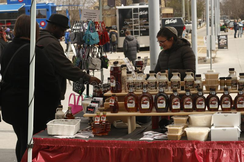 Elmira Canada, el 6 de abril de 2019: El diverso jarabe de arce relacionó mercancías en venta en una cabina de los vendedores E fotos de archivo libres de regalías