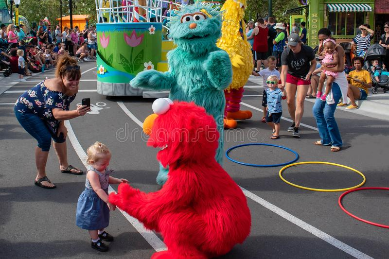 Elmo takes the hand of little girl in Sesame Street Party Parade at Seaworld. Orlando, Florida. November 06, 2019. Elmo takes the hand of little girl in Sesame royalty free stock photo