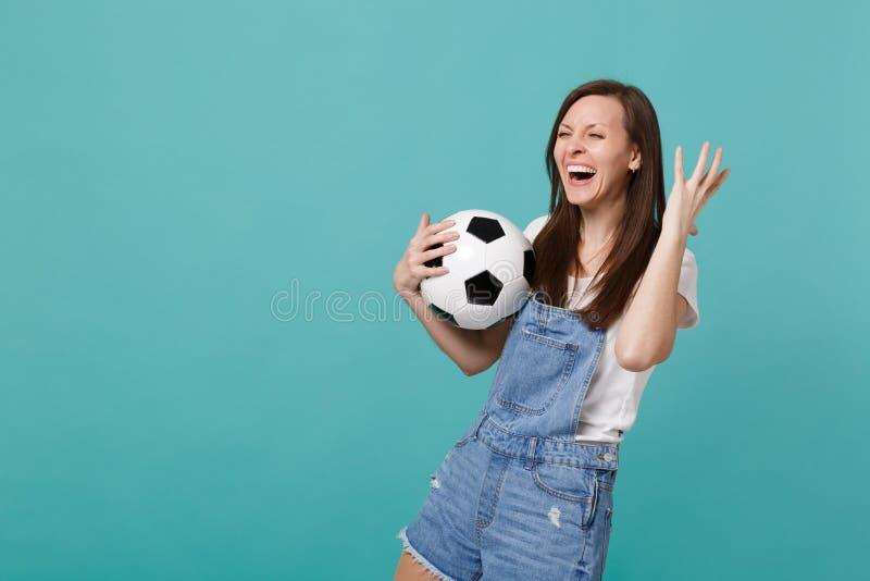 Elogio de riso do fan de futebol da jovem mulher acima da equipe favorita do apoio com a mão de aumentação da bola de futebol, ol fotografia de stock