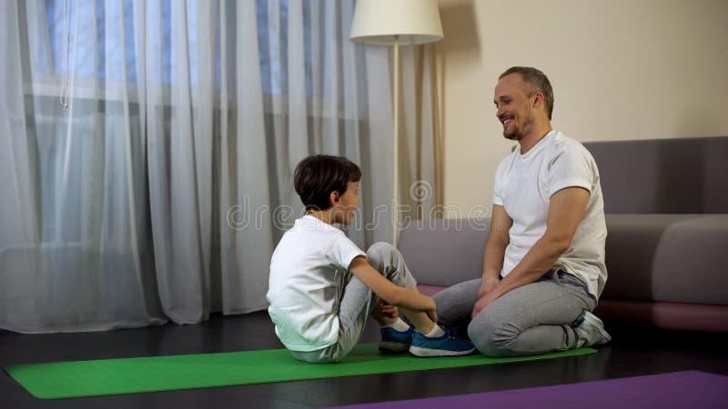 Elogio do pai e filho de apoio após a formação, exercitando em casa, esporte imagem de stock