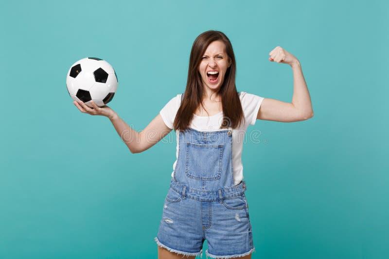 Elogio gritando forte do fan de futebol da mulher acima da equipe favorita do apoio com a bola de futebol que mostra o bíceps, mú fotografia de stock