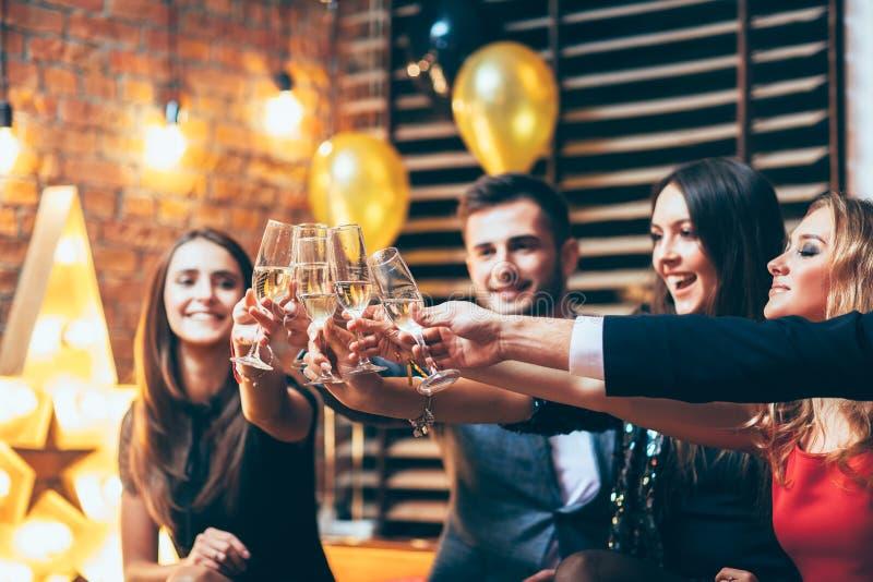 Elogios! Amigos com vidros do champanhe durante o celebrati do partido imagens de stock