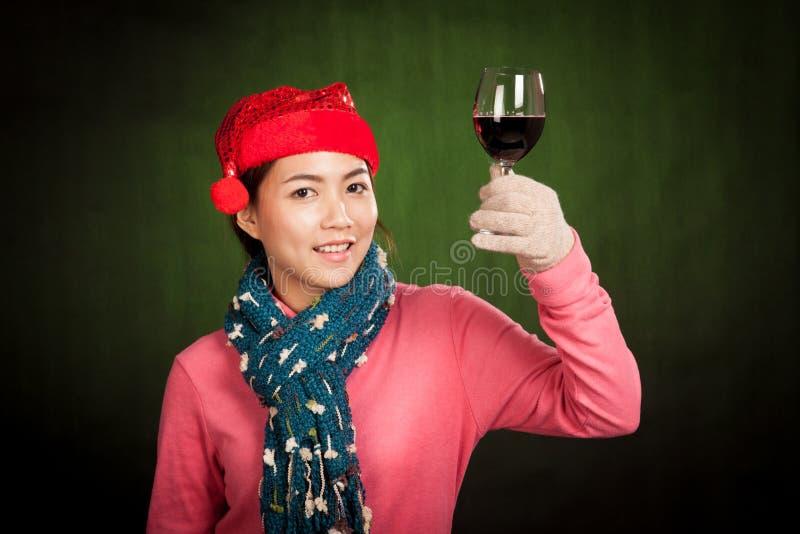 Elogios asiáticos do chapéu do Natal do desgaste da menina com vinho imagem de stock
