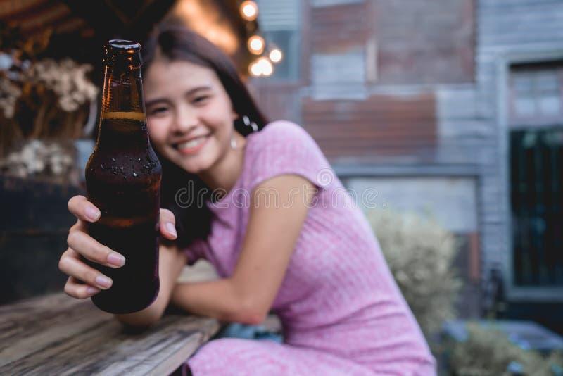 Elogios da mulher que bebem a garrafa de cerveja Alc do brinde do tinido da moça foto de stock royalty free