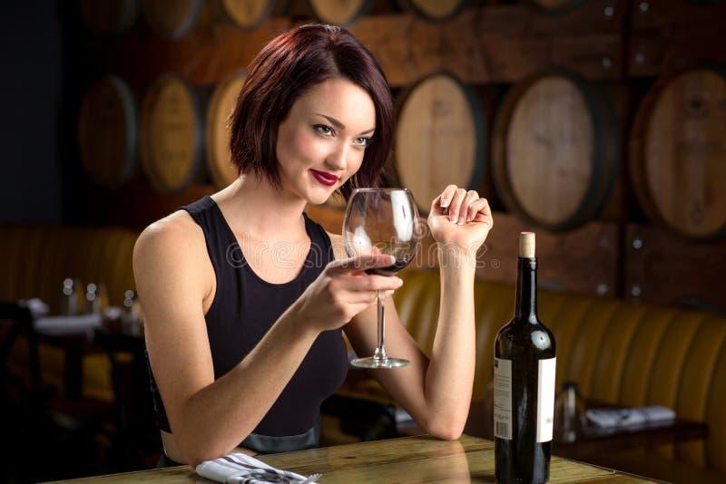 Elogios elegantes bonitos da mulher com a garrafa de vidro do vinho tinto no restaurante agradável da adega foto de stock