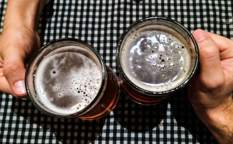 Elogios: mãos de um par que comemoram com cervejas imagens de stock