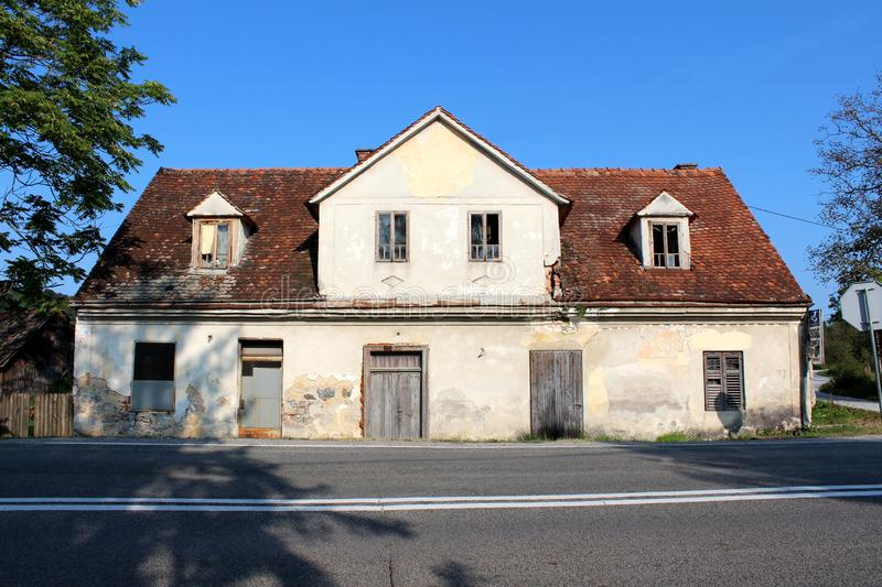 Elongated abandoned house with cracked facade and roof tiles broken windows and boarded doors next to paved road surrounded with. Tall trees and clear blue sky stock images