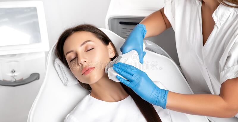 Elos epilation hair removal procedure on the face of a woman. Beautician doing laser rejuvenation in a beauty salon. Facial skin royalty free stock image