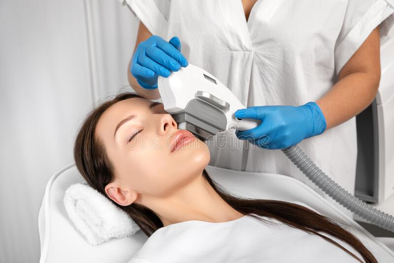 Elos epilation hair removal procedure on the face of a woman. Beautician doing laser rejuvenation in a beauty salon. Facial skin stock image