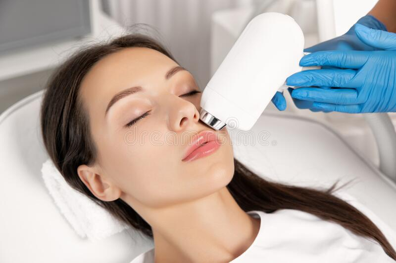 Elos epilation hair removal procedure on the face of a woman. Beautician doing laser rejuvenation in a beauty salon. Facial skin stock images