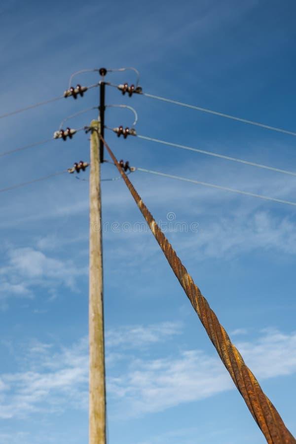Elströmpol och kablar som i höjden rymms av en närliggande metallkabel royaltyfri foto