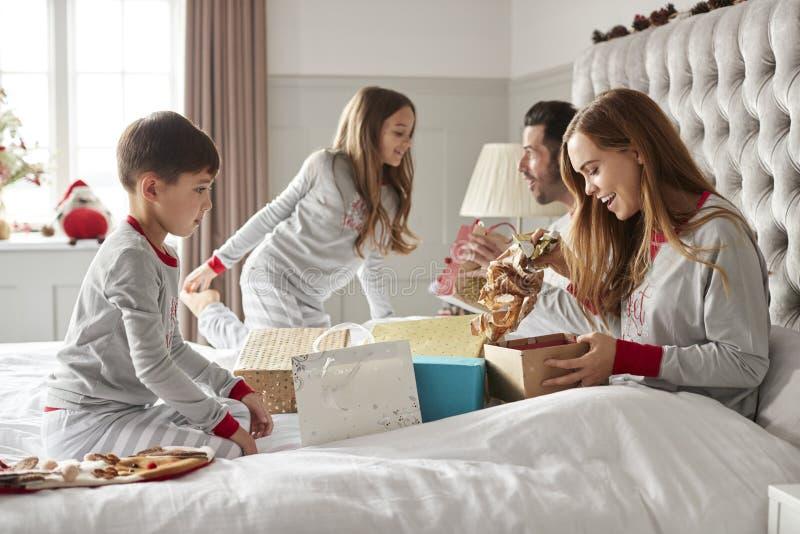 Eltern, die Geschenke von den Kindern wie sie Sit On Bed Exchanging Present am Weihnachtstag öffnen lizenzfreie stockbilder