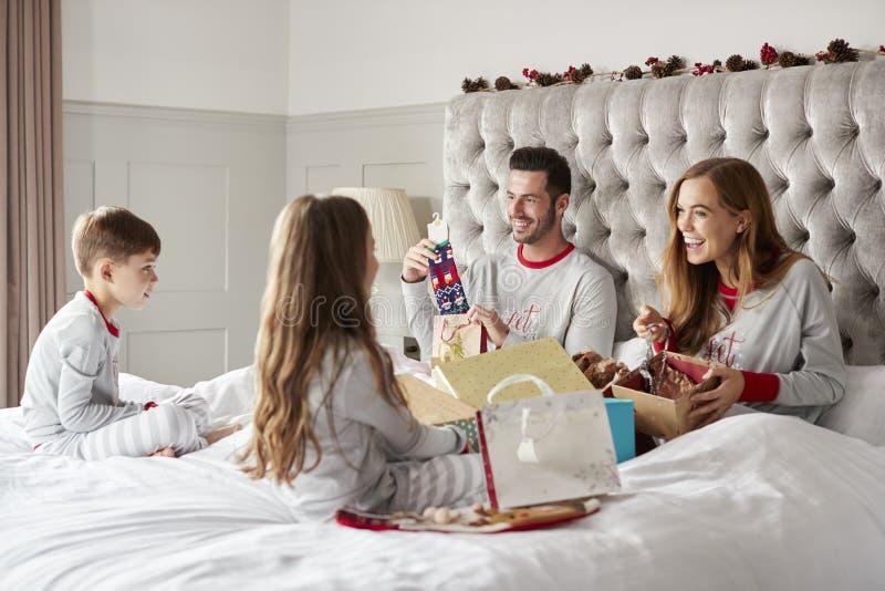 Eltern, die Geschenke von den Kindern wie sie Sit On Bed Exchanging Present am Weihnachtstag öffnen lizenzfreie stockfotos