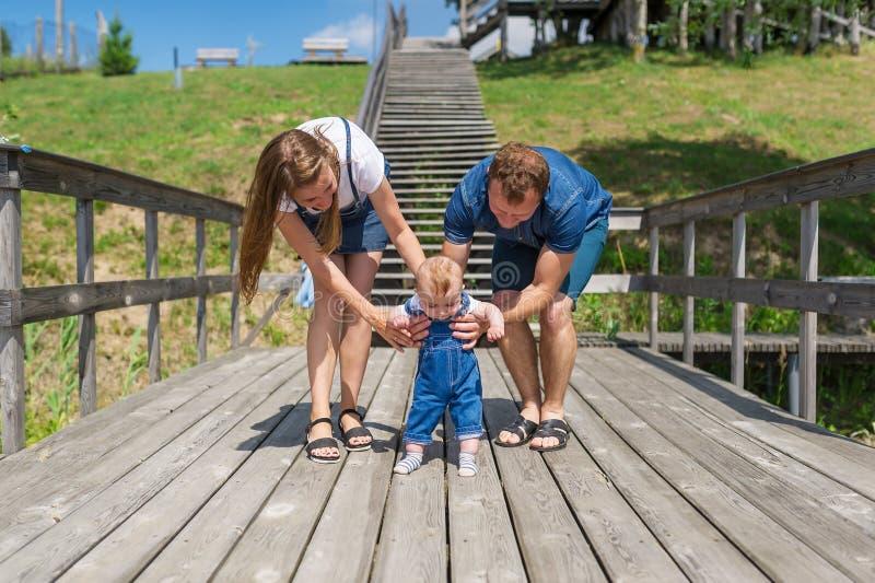 Eltern, die ihren kleinen Sohn macht erste Schritte halten lizenzfreie stockfotos