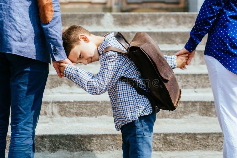 Eltern, die Kind zur Schule nehmen Schüler der Grundschule gehen Studie mit Rucksack draußen Muttervati und -sohn gehen Hand in H stockbild
