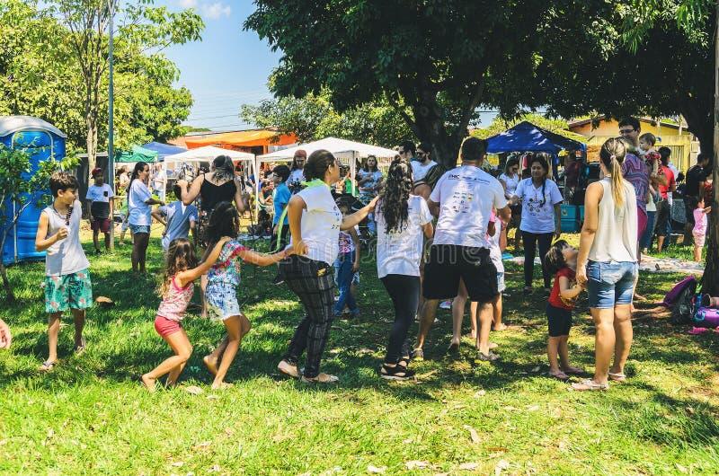 Eltern, die Kinder mit Spiel an der Freilichtmesse genannt unterhalten stockbild