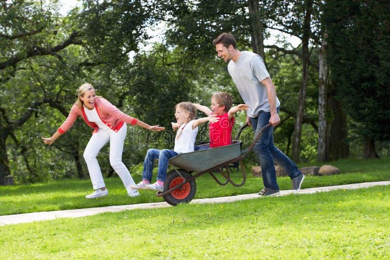 Eltern, die Kindern Fahrt in der Schubkarre geben lizenzfreie stockfotos