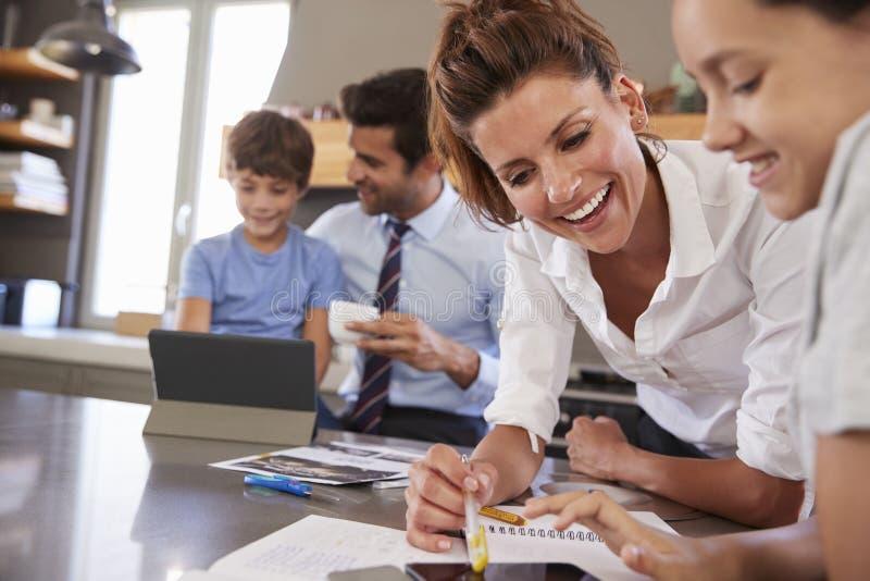 Eltern, die Kindern mit Hausarbeit bevor dem Gehen zu arbeiten helfen lizenzfreies stockfoto