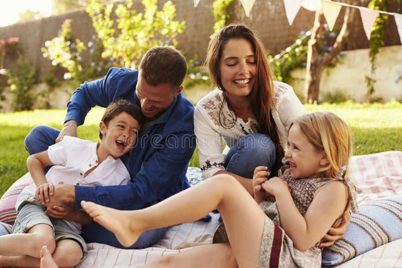 Eltern, die Spiel mit Kindern auf Decke im Garten spielen stockbild
