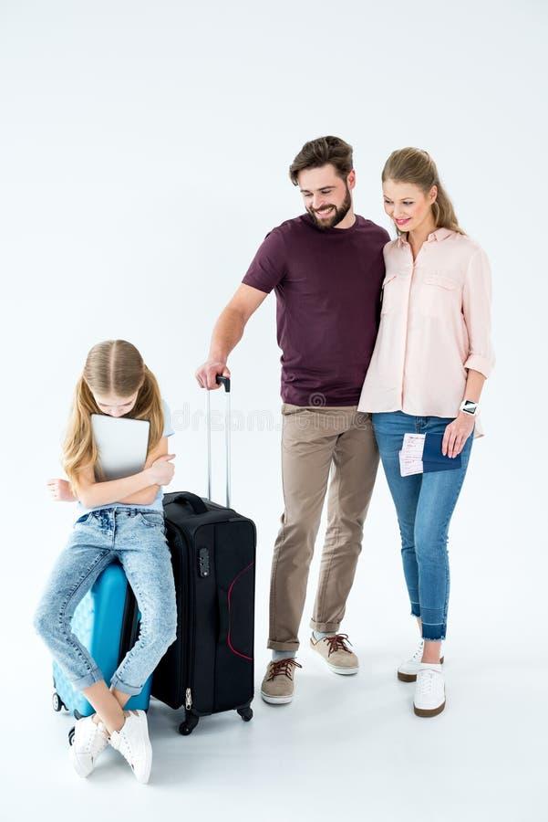 Eltern, die Umkippentochter mit der Tablette sitzt auf reisender Tasche betrachten lizenzfreie stockfotos