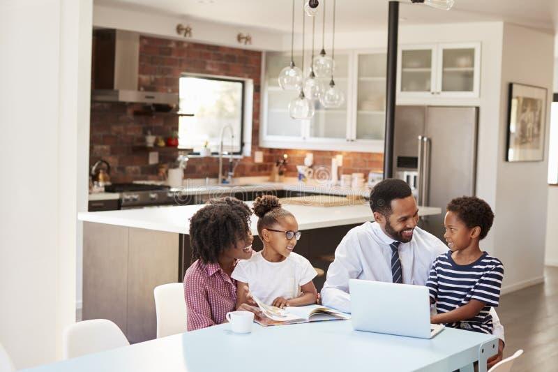 Eltern, die zu Hause um die Tabelle hilft Kindern mit Hausarbeit sitzen stockfotografie