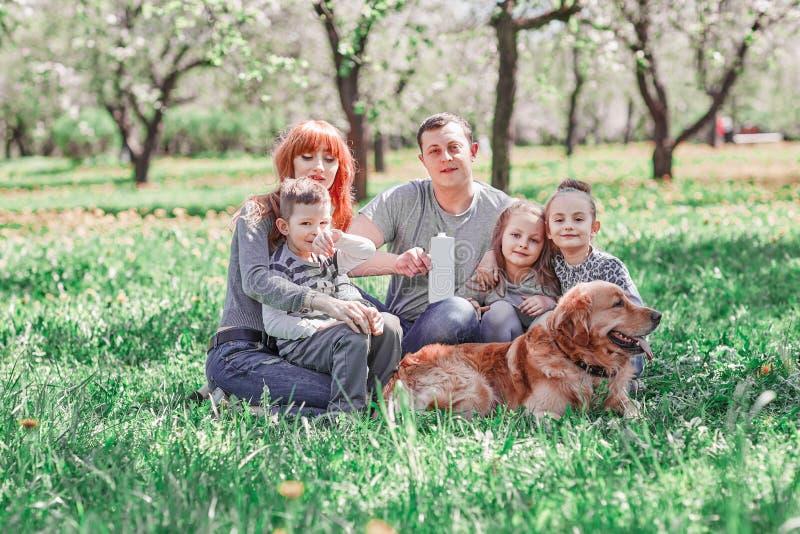 Eltern, Kinder und ihr Haustier, die auf dem Rasen an einem Sommertag sitzen stockbild
