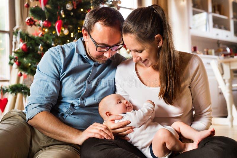 Eltern mit Baby vor Weihnachtsbaum lizenzfreies stockbild