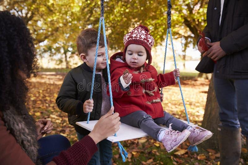 Eltern mit den Kindern, die auf Baum-Schwingen in Autumn Garden spielen stockfotografie