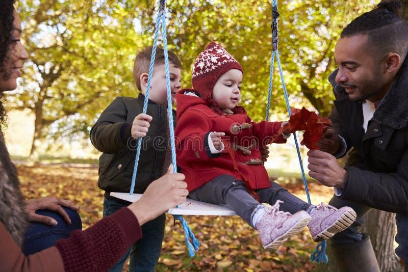 Eltern mit den Kindern, die auf Baum-Schwingen in Autumn Garden spielen lizenzfreie stockbilder