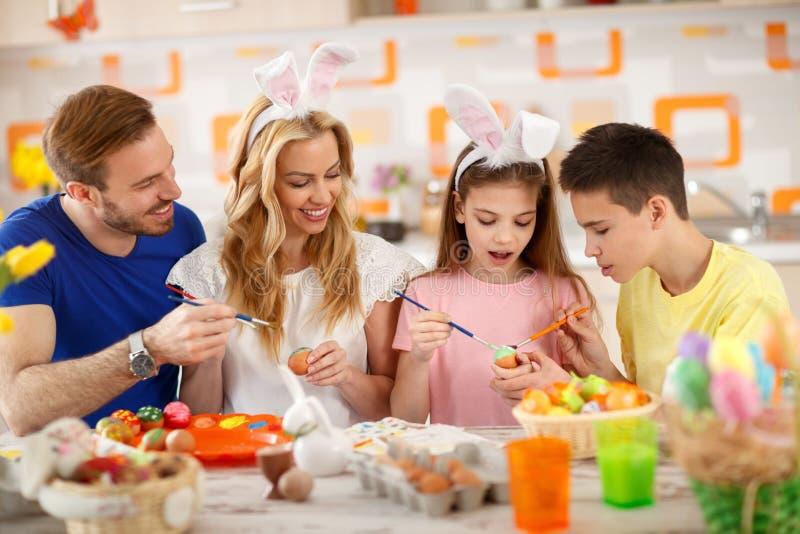 Eltern mit den Kindern, die bunte Eier malen stockfotografie