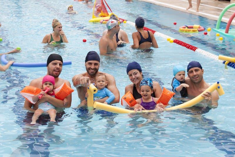 Eltern mit den Kindern, die im Pool spielen stockfoto