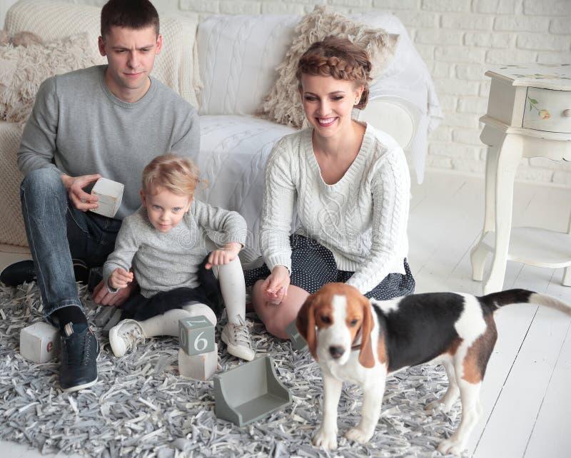 Eltern mit einer jungen Tochter und einem Haustier, die auf der Couch sitzen lizenzfreies stockfoto