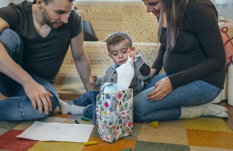 Eltern mit ihrem kleinen Sohn, der ein Geschenk öffnet stockbilder