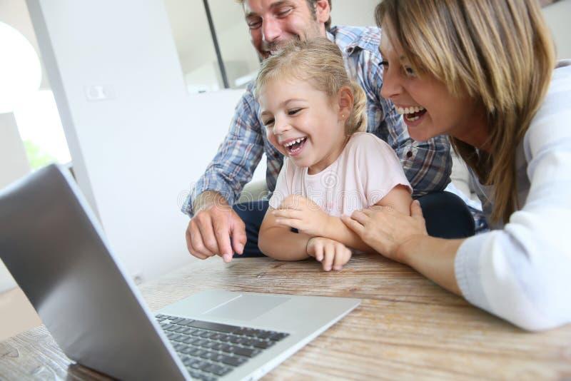 Eltern mit ihrer Tochter, die vor Laptop lacht stockbilder