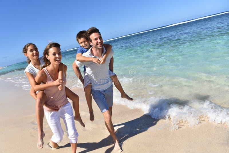 Eltern mit Kindern auf dem hinteren Betrieb durch das Meer lizenzfreie stockfotografie