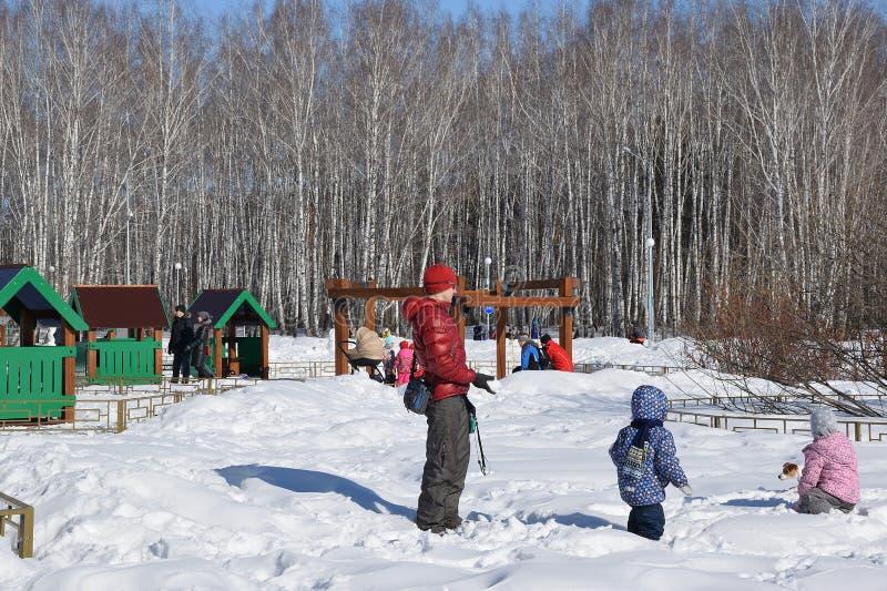 Eltern mit Kindern gehen in den Winterpark stockbild