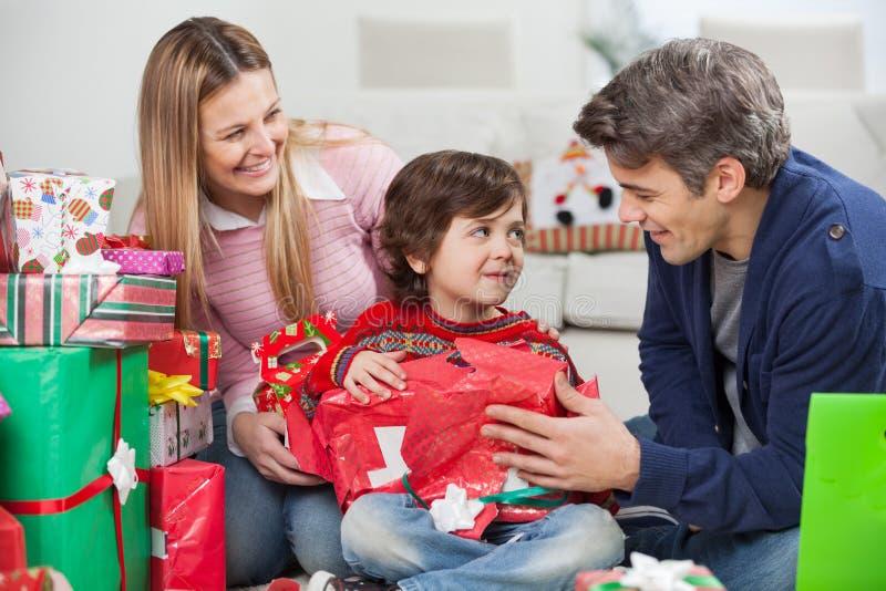 Eltern mit Sohn-Öffnungs-Weihnachtsgeschenk lizenzfreie stockfotos