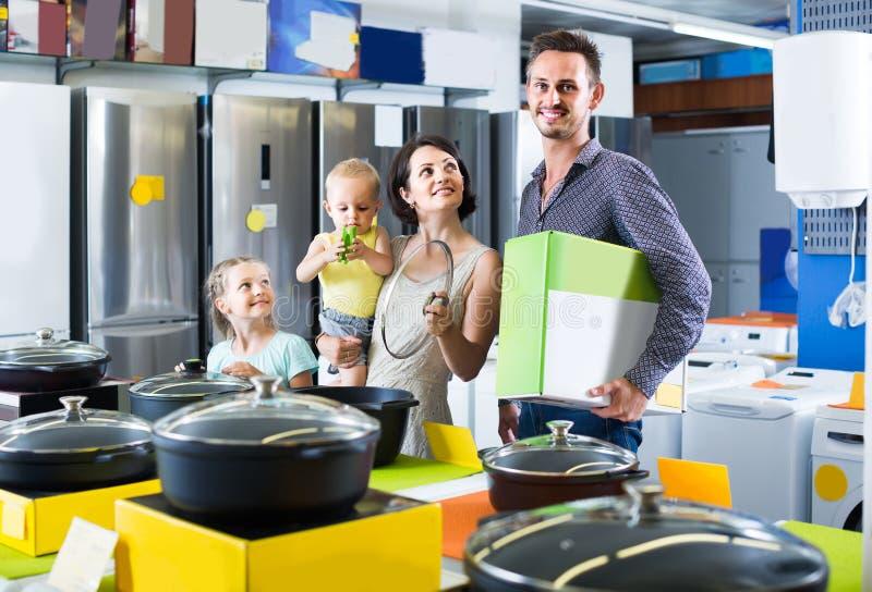 Eltern mit zwei Kindern, die Küchengeschirr in Haushaltsgerät sto wählen stockfotografie