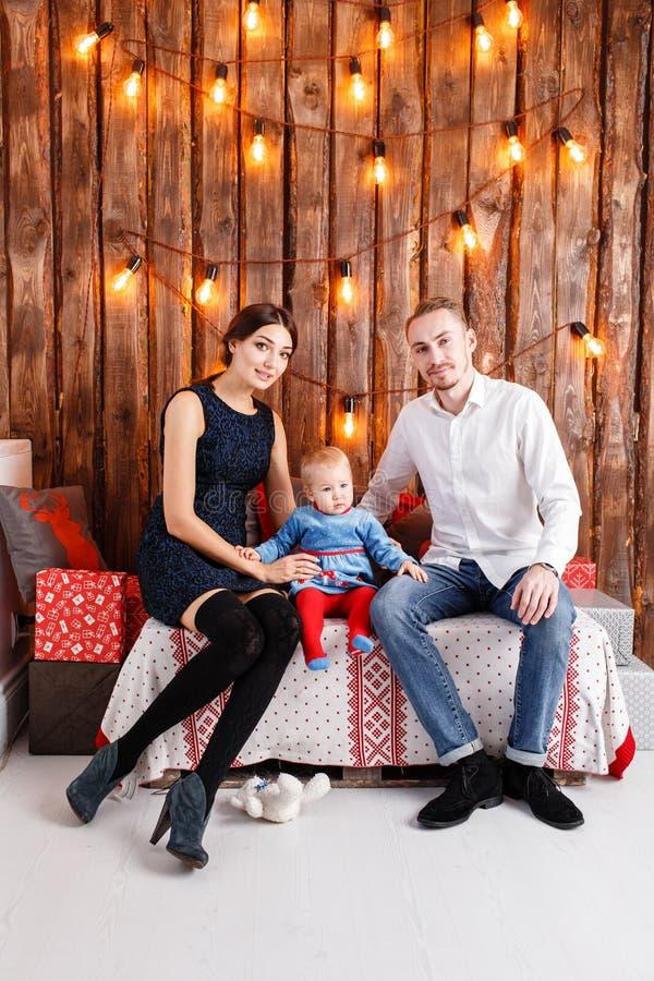 Eltern und Kind, die Spaß im Dachboden-ähnlichen Raum, hölzerner rustikaler Hintergrund mit einer Girlande von Birnen haben Liebe stockbild