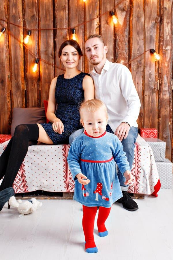 Eltern und Kind, die Spaß im Dachboden-ähnlichen Raum, hölzerner rustikaler Hintergrund mit einer Girlande von Birnen haben Liebe lizenzfreies stockfoto