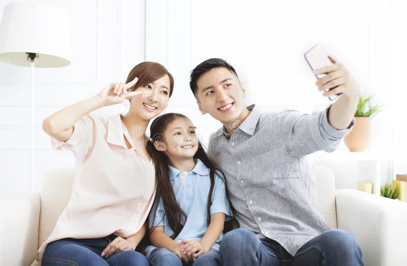 Eltern und Kind, die zusammen selfie nehmen stockbilder
