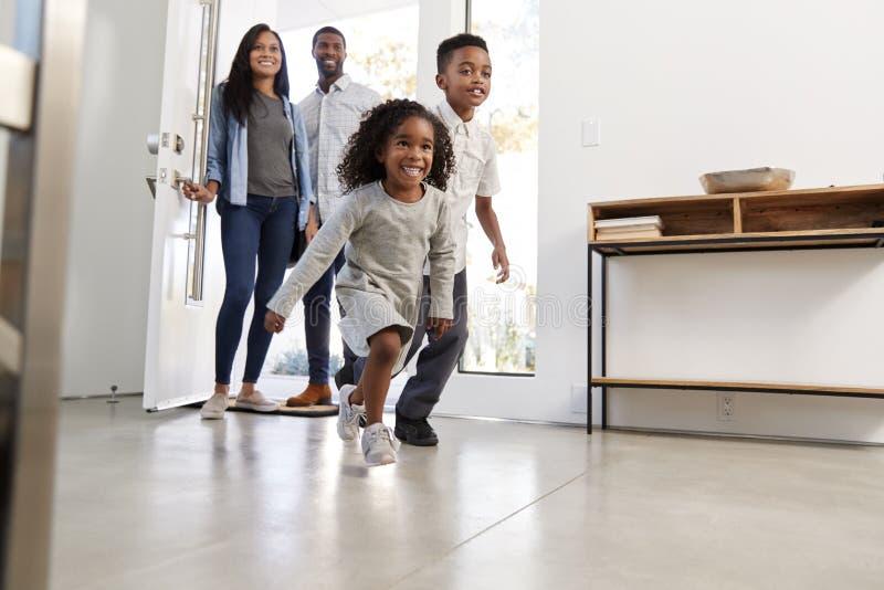 Eltern und Kinder, die Hauptöffnung Front Door And Running Inside zurückbringen lizenzfreies stockfoto
