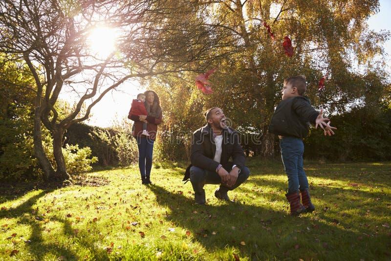 Eltern und Kinder, die mit Autumn Leaves im Garten spielen stockfotografie