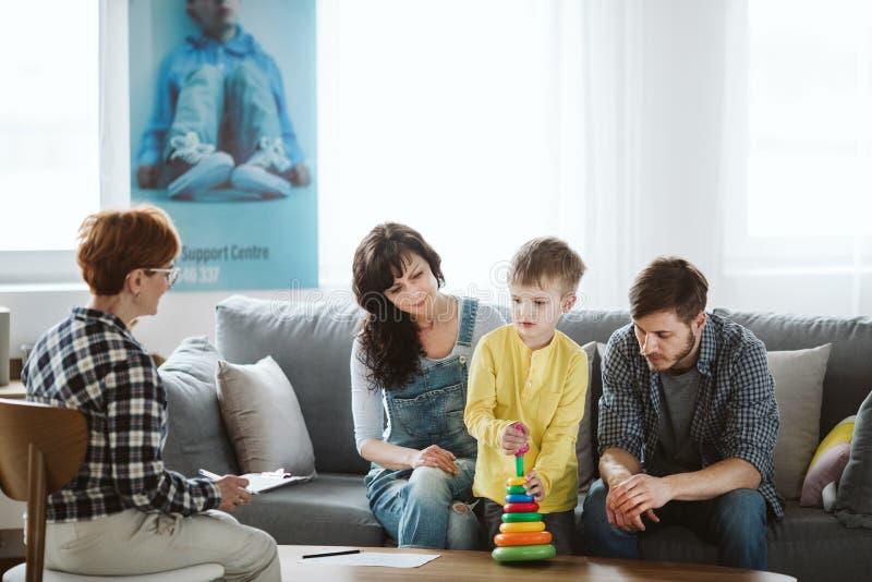 Eltern und Therapeut sitzen auf der Couch w?hrend einer Sitzung ?ber ihr Kind lizenzfreies stockfoto