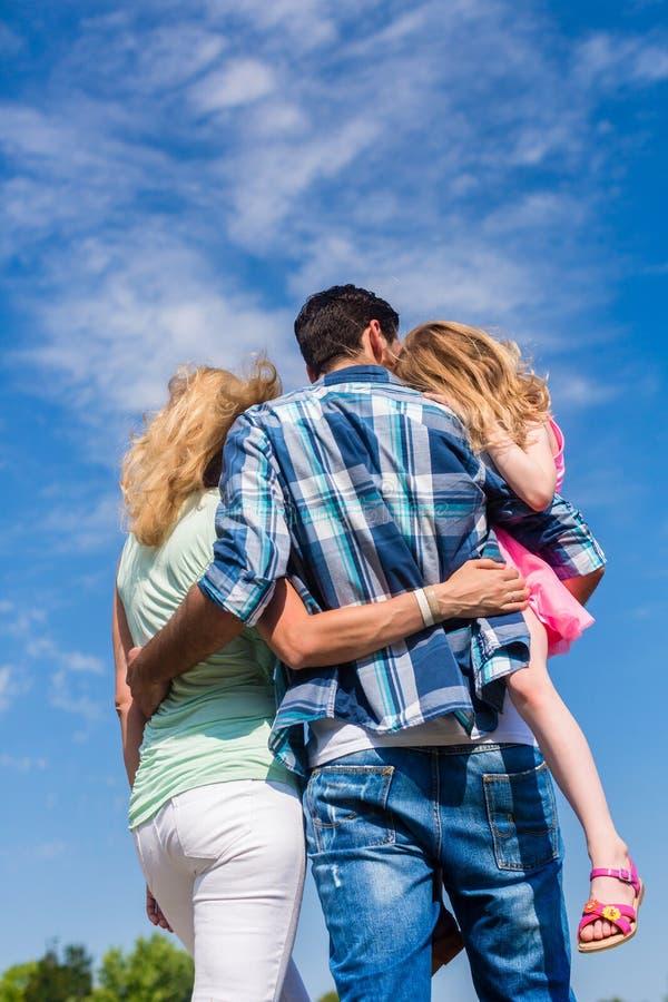Eltern und Tochter, Arm im Arm in der hinteren Ansicht stockfotografie
