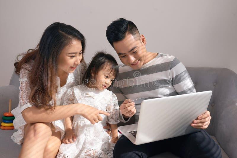 Eltern und Tochter, die zusammen mit einem Laptop auf einer Couch spielen lizenzfreies stockbild
