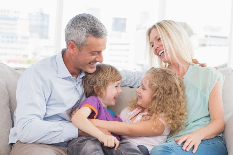 Eltern, welche die Kinder zu Hause umarmen betrachten lizenzfreies stockbild